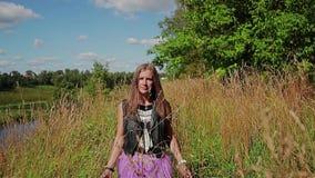 Ένα νέο κορίτσι περπατά κατά μήκος της πορείας μέσω της ψηλής ξηράς χλόης που ωθεί το χέρι της και εξετάζει τη κάμερα Ο ήλιος λάμ απόθεμα βίντεο