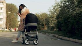 Ένα νέο κορίτσι περπατά μέσω του πάρκου με μια μεταφορά μωρών και μιλά στο τηλέφωνο φιλμ μικρού μήκους