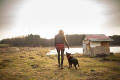Ένα νέο κορίτσι περπατά με το σκυλί της στην ακτή μιας λίμνης Πίσω άποψη στοκ εικόνα με δικαίωμα ελεύθερης χρήσης