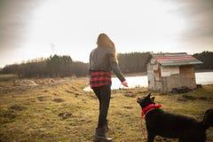 Ένα νέο κορίτσι περπατά με το σκυλί της στην ακτή μιας λίμνης Πίσω άποψη στοκ φωτογραφία με δικαίωμα ελεύθερης χρήσης
