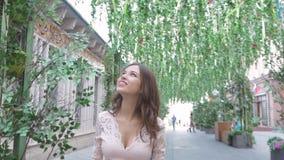 Ένα νέο κορίτσι περπατά τις οδούς της πόλης Όμορφες διακοσμήσεις λουλουδιών ν το καλοκαίρι μια ηλιόλουστη ημέρα απόθεμα βίντεο