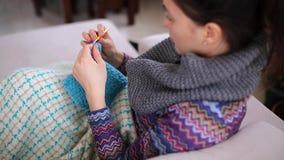 Ένα νέο κορίτσι πλέκει ένα θερμό τσιγγελάκι μαντίλι φιλμ μικρού μήκους