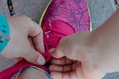 Ένα νέο κορίτσι που δένει τις δαντέλλες των τρέχοντας παπουτσιών της προτού να πάει για ένα τρέξιμο στοκ φωτογραφίες με δικαίωμα ελεύθερης χρήσης