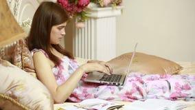 Ένα νέο κορίτσι που εργάζεται στον υπολογιστή στο κρεβάτι Κοινωνικά δίκτυα φιλμ μικρού μήκους