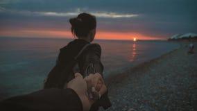 Ένα νέο κορίτσι που κρατά το χέρι ενός τύπου Όμορφο κορίτσι στην παραλία στο ηλιοβασίλεμα φιλμ μικρού μήκους