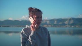 Ένα νέο κορίτσι που μιλά σε ένα κινητό τηλέφωνο στη λίμνη στο υπόβαθρο της πόλης στις ακτίνες του ήλιου στο ηλιοβασίλεμα απόθεμα βίντεο