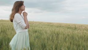 Ένα νέο κορίτσι που προσεύχεται σε έναν τομέα σίτου, μια γυναίκα μεταξύ των αυτιών του καλαμποκιού που απολαμβάνει τη φύση και πο φιλμ μικρού μήκους