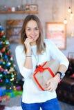 Ένα νέο κορίτσι που στέκεται με δεμένη τη δώρο κόκκινη κορδέλλα στο smili χεριών Στοκ φωτογραφίες με δικαίωμα ελεύθερης χρήσης
