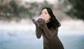 Ένα νέο κορίτσι που φυσά στο χιόνι Στοκ φωτογραφία με δικαίωμα ελεύθερης χρήσης