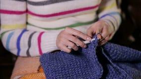 Ένα νέο κορίτσι πλέκει μια συνεδρίαση φιλέδων μαντίλι στον καναπέ που καλύπτεται με ένα κάλυμμα απόθεμα βίντεο