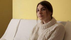 Ένα νέο κορίτσι σε ένα άνετο θερμό πουλόβερ σε ένα χειμερινό βράδυ που πίνει το τσάι και που σκέφτεται στο σπίτι για κάτι απόθεμα βίντεο