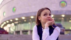 Ένα νέο κορίτσι σε ένα άσπρες πουκάμισο και μια φανέλλα, που κάθονται έξω το βράδυ, αναμονή για μια συνεδρίαση απόθεμα βίντεο