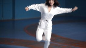 Ένα νέο κορίτσι σε ένα άσπρο αθλητικό κοστούμι εκτελεί karate τις τεχνικές στην αθλητική αίθουσα Κωμικός αθλητισμός φιλμ μικρού μήκους