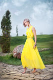 Ένα νέο κορίτσι σε ένα κίτρινο φόρεμα στοκ φωτογραφίες