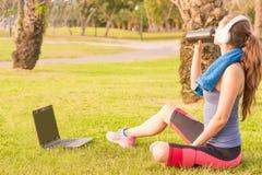 Ένα νέο κορίτσι σε ένα πάρκο στη χλόη μετά από την κατάρτιση ικανότητας με το lap-top και τα ακουστικά και πίνει το πρωτεϊνικό κο στοκ εικόνες