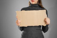 Ένα νέο κορίτσι σε ένα γκρίζο σακάκι που κρατά ένα κομμάτι του χαρτονιού prep στοκ φωτογραφίες