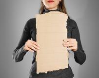 Ένα νέο κορίτσι σε ένα γκρίζο σακάκι που κρατά ένα κομμάτι του χαρτονιού prep στοκ εικόνα με δικαίωμα ελεύθερης χρήσης