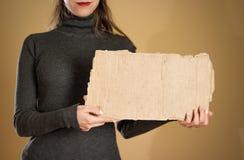 Ένα νέο κορίτσι σε ένα γκρίζο σακάκι που κρατά ένα κομμάτι του χαρτονιού prep στοκ φωτογραφία με δικαίωμα ελεύθερης χρήσης