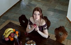 Ένα νέο κορίτσι σε ένα εκλεκτής ποιότητας φόρεμα κάθεται σε έναν πίνακα στοκ φωτογραφίες με δικαίωμα ελεύθερης χρήσης