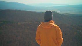 Ένα νέο κορίτσι σε ένα κίτρινο σακάκι και μια γκρίζα ΚΑΠ στέκεται στο βουνό, με την πίσω στο πλαίσιο φιλμ μικρού μήκους