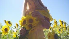 Ένα νέο κορίτσι σε ένα κίτρινο φόρεμα με τους ηλίανθους στα χέρια της Κινηματογράφηση σε πρώτο πλάνο απόθεμα βίντεο