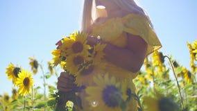 Ένα νέο κορίτσι σε ένα κίτρινο φόρεμα με τους ηλίανθους στα χέρια της Κινηματογράφηση σε πρώτο πλάνο φιλμ μικρού μήκους