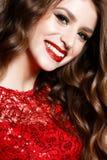Ένα νέο κορίτσι σε ένα λαμπρά κόκκινα φόρεμα και ένα βράδυ makeup Όμορφο πρότυπο χαμόγελου στην εικόνα ενός νέου έτους με τις μπο στοκ εικόνα