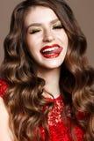 Ένα νέο κορίτσι σε ένα λαμπρά κόκκινα φόρεμα και ένα βράδυ makeup Όμορφο πρότυπο χαμόγελου στην εικόνα ενός νέου έτους με τις μπο στοκ εικόνες με δικαίωμα ελεύθερης χρήσης