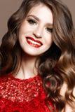 Ένα νέο κορίτσι σε ένα λαμπρά κόκκινα φόρεμα και ένα βράδυ makeup Όμορφο πρότυπο χαμόγελου στην εικόνα ενός νέου έτους με τις μπο στοκ φωτογραφία