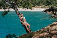 Ένα νέο κορίτσι σε ένα μαγιό στέκεται σε έναν απότομο βράχο επάνω από τη θάλασσα Το πρότυπο απολαμβάνουν μια θερινή ημέρα Στοκ Φωτογραφία