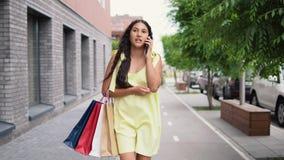 Ένα νέο κορίτσι σε ένα μακρύ φόρεμα περπατά γύρω από την πόλη μετά από να ψωνίσει και να μιλήσει στο τηλέφωνο 4K απόθεμα βίντεο