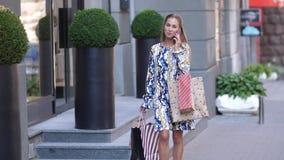 Ένα νέο κορίτσι σε ένα μακρύ φόρεμα περπατά γύρω από την πόλη μετά από να ψωνίσει και να μιλήσει στο τηλέφωνο 4k σε αργή κίνηση φιλμ μικρού μήκους