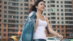 Ένα νέο κορίτσι σε μια άσπρη μπλούζα και τα τζιν είναι μεταξύ των υψηλών σύγχρονων κατοικημένων σπιτιών απόθεμα βίντεο