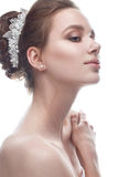 Ένα νέο κορίτσι σε μια ευγενή γαμήλια εικόνα με diadem στο κεφάλι της Το όμορφο πρότυπο στην εικόνα της νύφης σε ένα λευκό απομόν Στοκ Φωτογραφίες