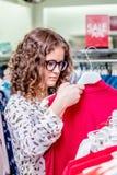 Ένα νέο κορίτσι σε μια καθιερώνουσα τη μόδα μπουτίκ εξετάζει ένα κόκκινο φόρεμα Μοντέρνα ενδύματα αγορών στοκ φωτογραφίες με δικαίωμα ελεύθερης χρήσης