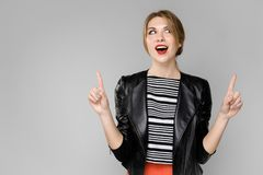 Ένα νέο κορίτσι σε ένα σακάκι δέρματος παρουσιάζει στους αντίχειρες χεριών της Πορτρέτο ενός κοριτσιού με τα ξανθά μαλλιά σε ένα  στοκ εικόνα με δικαίωμα ελεύθερης χρήσης