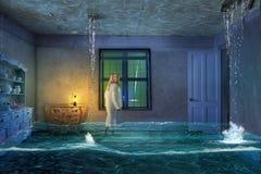 Ένα νέο κορίτσι σε ένα σπίτι κατά τη διάρκεια μιας πλημμύρας στοκ εικόνες