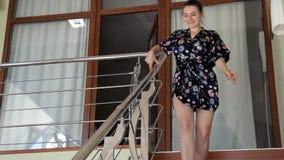 Ένα νέο κορίτσι στέκεται στο δεύτερο όροφο του σπιτιού της και κατεβαίνει μια ξύλινη σκάλα φιλμ μικρού μήκους