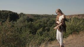 Ένα νέο κορίτσι στέκεται στο υπόβαθρο της φύσης απόθεμα βίντεο