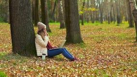Ένα νέο κορίτσι στα άρθρα φθινοπώρου πάρκων, χαμόγελου, σκέψης και δακτυλογράφησης σε ένα lap-top απόθεμα βίντεο