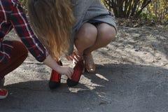 Ένα νέο κορίτσι στην οδό βγάζει τα περιστασιακά παπούτσια της και βάζει στα ενδύματα διακοπών στοκ φωτογραφία με δικαίωμα ελεύθερης χρήσης