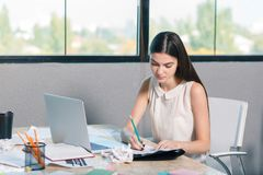 Ένα νέο κορίτσι στο γραφείο και αφθονίες επάνω στα έγγραφα Μέσα στο γραφείο Στοκ φωτογραφίες με δικαίωμα ελεύθερης χρήσης
