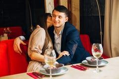 Ένα νέο κορίτσι στο εστιατόριο που φιλά το φίλο της Στοκ Φωτογραφία