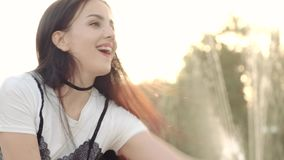 Ένα νέο κορίτσι στο ηλιοβασίλεμα παίζει coquettishly με το νερό σε μια πηγή πόλεων φιλμ μικρού μήκους