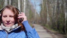 Ένα νέο κορίτσι στο πάρκο που ακούει τη μουσική στα ακουστικά Μια γυναίκα περπατά μέσω του πάρκου άνοιξη και απολαμβάνει τη μουσι απόθεμα βίντεο