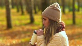 Ένα νέο κορίτσι στο πάρκο φθινοπώρου, που στέκεται λοξά, καυτός καφές κατανάλωσης, που εξετάζει την απόσταση φιλμ μικρού μήκους
