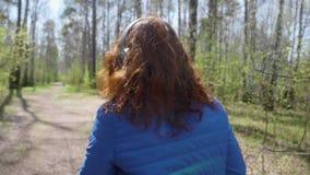 Ένα νέο κορίτσι στο πάρκο φορά τα ακουστικά για να ακούσει τη μουσική Μια γυναίκα πηγαίνει μέσα για τον αθλητισμό και απολαμβάνει απόθεμα βίντεο