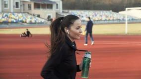 Ένα νέο κορίτσι τρέχει σε ένα treadmill στάδιο με ένα μπουκάλι κατανάλωσης υπό εξέταση φιλμ μικρού μήκους