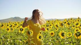 Ένα νέο κορίτσι τρεξίματα στα κίτρινα φορεμάτων πέρα από τον τομέα στους ηλίανθους κίνηση αργή φιλμ μικρού μήκους