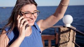 Ένα νέο κορίτσι υπερασπίζεται τη θάλασσα που μιλά στο τηλέφωνο, ο αέρας αναπτύσσει την τρίχα της απόθεμα βίντεο